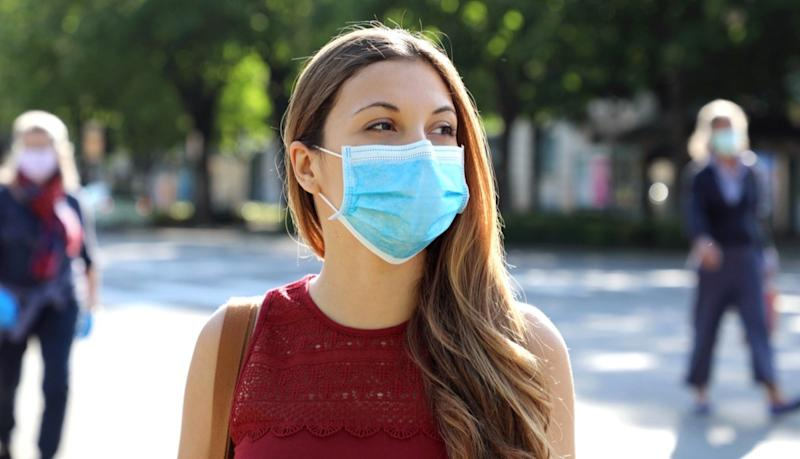 Social Distancing Woman in city street wearing surgical mask against disease virus SARS-CoV-2.