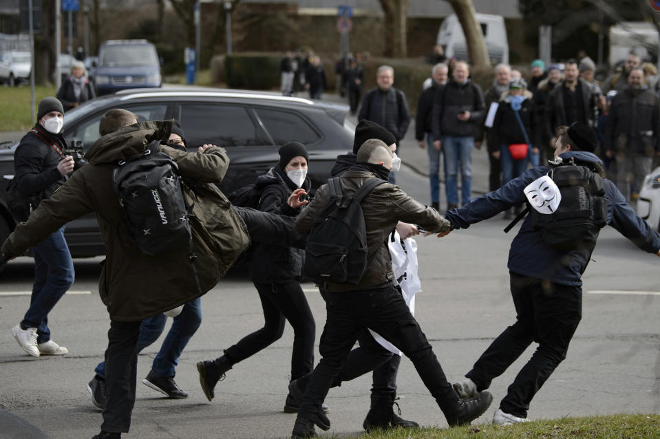 "Participants scuffle at a rally under the slogan ""Free citizens Kassel - basic rights and democracy"" in Kassel, Germany, Saturday, March 20, 2021. According to police, several thousand people were on the move in the city center and disregarded the instructions of the authorities during the unregistered demonstration against Corona measures. (Swen Pfoertner/dpa via AP)"