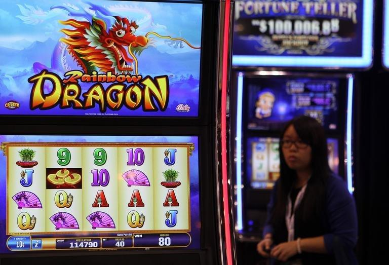 A woman walks past gaming machines at the G2E Asia gaming expo in Macau on May 22, 2012