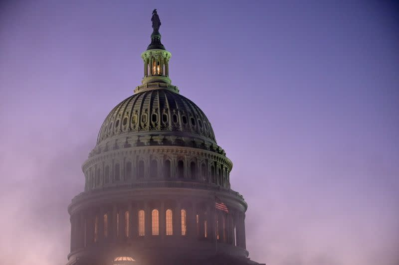 The U.S. Capitol dome is seen through steam from a vent at sunset in Washington