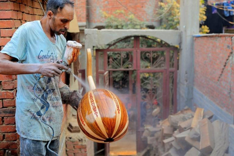 A worker sprays varnish onto an oud at a workshop in the Al-Marg district on the outskirts of the Egyptian capital Cairo