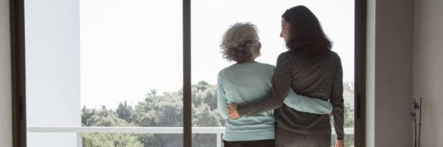 Mother and daughter embracing while looking out a window.