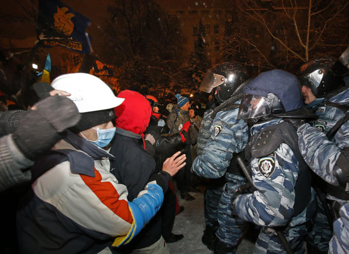 Riot police push away pro-European Union activists from their barricades at the Ukrainian presidential administration building in Kiev, Ukraine, Tuesday, Dec. 10, 2013. Heavily armed riot troops broke into the offices of a top Ukrainian opposition party in Kiev and seized its servers Monday, the party said, as anti-government protests crippled the capital for yet another day. Elsewhere police dismantled or blocked off several small protest tent camps set up near key national government buildings in the city. (AP Photo/Alexander Zemlianichenko)