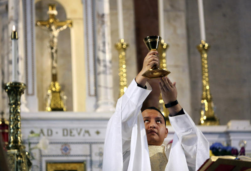 In this April 19, 2020, photo, the Rev. Joseph Dutan, 32, lifts the chalice during Sunday Mass at an empty St. Brigid Church in the Brooklyn borough of New York. Dutan recalls how he lifted the chalice in the empty church and felt a flood of emotions: grief, the pain of isolation, even doubt. But also, the promise of hope that is the gift of every Easter -- even in the midst of a pandemic that had already robbed him and his community of so much, and threatened to take so much more. (AP Photo/Jessie Wardarski)