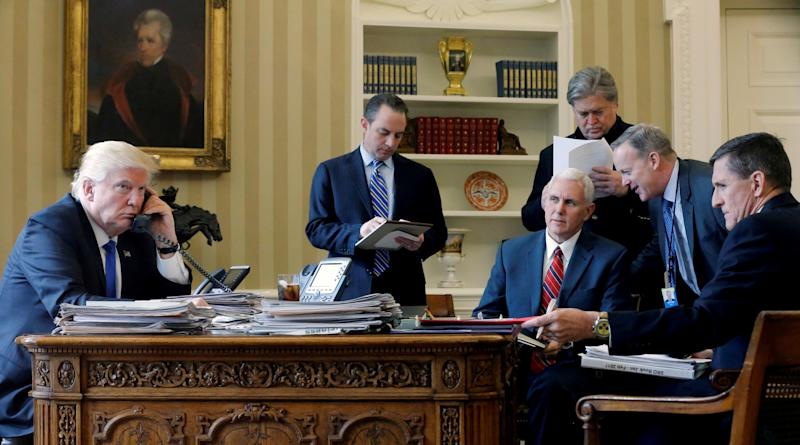 President Donald Trump is joined by Chief of Staff Reince Priebus, center, Vice President Mike Pence, senior adviser Steve Bannon, Communications Director Sean Spicer and national security advisor Michael Flynn as he speaks by phone with Russia's President Vladimir Putin from the Oval Office on Jan. 28. (Jonathan Ernst / Reuters)