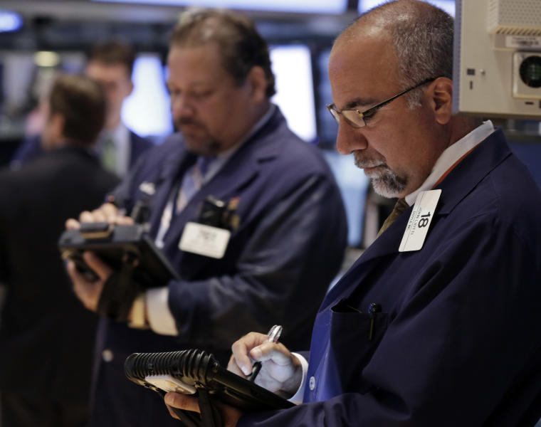 In this Tuesday, Aug. 13, 2013 photo, trader John Santiago, left, and John Liotti work on the floor of the New York Stock Exchange. Wall Street appears headed for a lower opening Wednesday, Aug. 21, 2013, based on futures trading. (AP Photo/Richard Drew)
