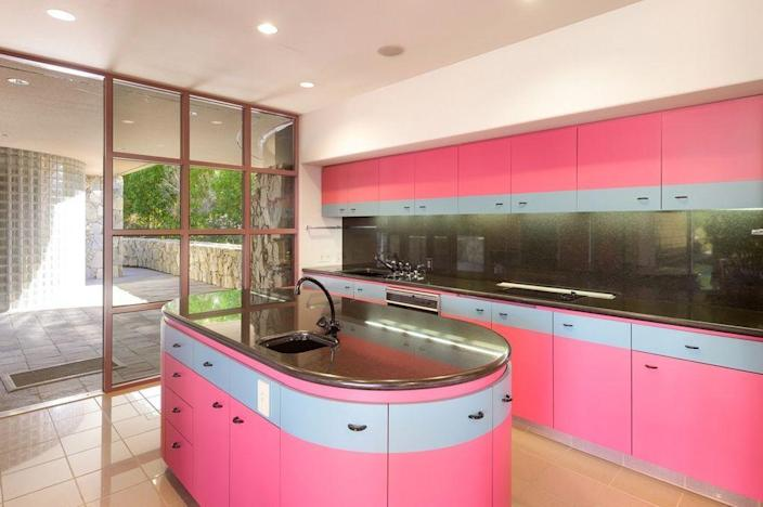 A bright pink kitchen decorated in the iconic style of the 1980s.
