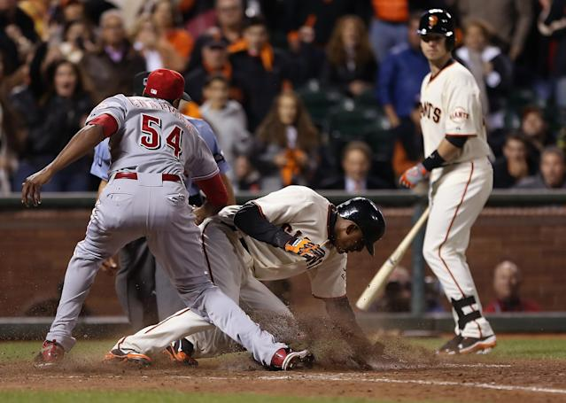 SAN FRANCISCO, CA - OCTOBER 06: Joaquin Arias #13 of the San Francisco Giants scores on a past ball by pitcher Aroldis Chapman of the Cincinnati Reds in the ninth inning during Game One of the National League Division Series at AT&T Park on October 6, 2012 in San Francisco, California. The Reds defeated the Giants 5-2. (Photo by Jeff Gross/Getty Images)