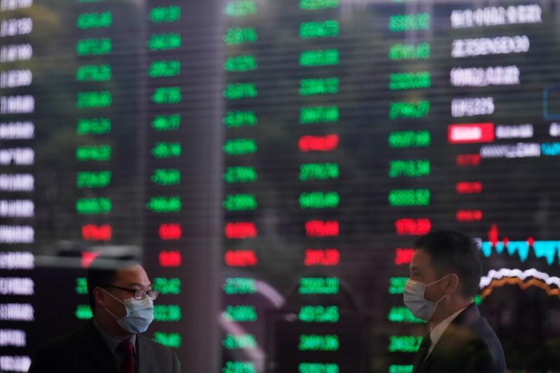 Men wearing face masks are seen inside the Shanghai Stock Exchange building, as the country is hit by a novel coronavirus outbreak, at the Pudong financial district in Shanghai