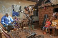 Emmanuel Wembe, centre, gets to work customising a motorbike for heavy duty