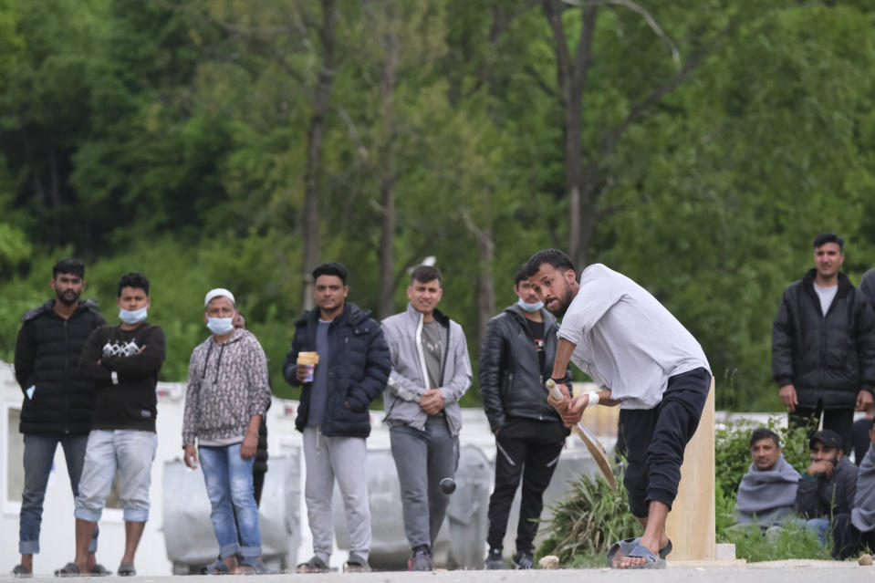 A batter plays a forward defensive as migrants play a game of cricket in Blazuj migrant camp in Bosnia's capital of Sarajevo Wednesday, May 19, 2021. (AP Photo/Kemal Softic)