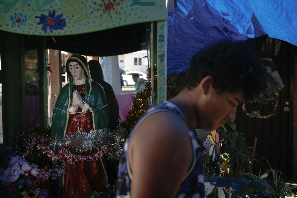 Noel Mata walks past a statue of Our Lady of Guadalupe made by his parents in the Watts neighborhood of Los Angeles, Monday, Aug. 3, 2020. Watts has changed demographically from an exclusively Black neighborhood in the '60s to one that's majority Latino. But it remains a poor neighborhood with high unemployment. (AP Photo/Jae C. Hong)