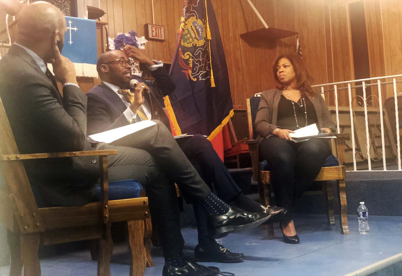 """In this Jan. 16, 2020, photo, from left, Harrison Floyd and Paris Dennard of President Donald Trump's reelection campaign black voter outreach effort and Kamilah Prince, the Republican National Committee's director of African American engagement participate in a """"Black Voices for Trump"""" event at Philadelphia's First Immanuel Baptist Church. Trump's reelection campaign is reaching out to black voters through one of their communities' most important institutions — black churches.  (AP Photo/Elana Schor)"""