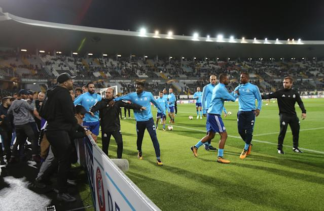 Patric Evra is restrained by teammates during a confrontation with fans before a Europa League match in Portugal.