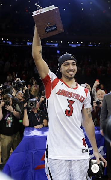 Louisville's Peyton Sivacelebrates while holding the most valuable payer trophy after an NCAA college basketball game against Syracuse for the Big East Conference men's tournament title, Saturday, March 16, 2013, in New York. Louisville won 78-61. (AP Photo/Frank Franklin II)