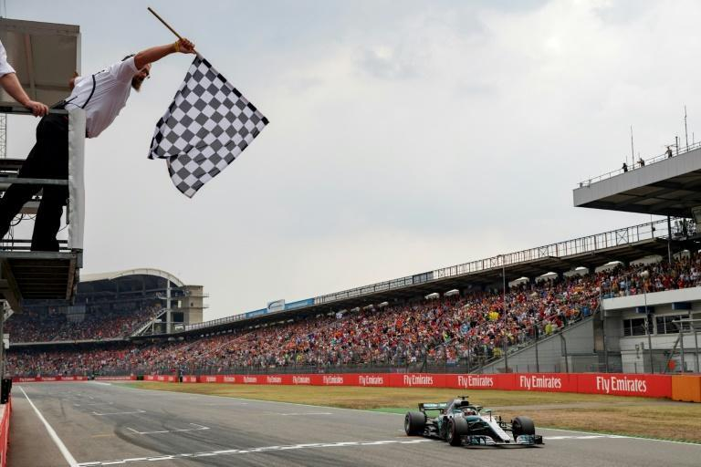 On the charge: Lewis Hamilton took the German GP after a brilliant drive in the rain after qualifying 14th (AFP/VALDRIN XHEMAJ)