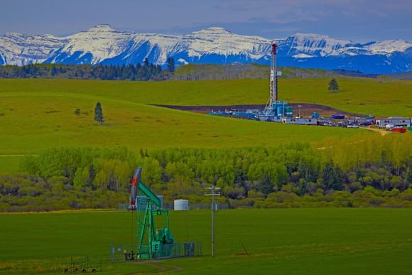 Drilling rig and pump jack with mountain range in background.