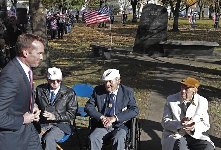 Eric Fanning, left, acting Secretary of the US Air Force walks to the podium past three of the surviving members, seated left to right, Edward Saylor, David Thatcher, and Richard Cole, of the 1942 raid on Tokyo led by Lt. Col. Jimmy Doolittle, Saturday, Nov. 9, 2013, outside the National Museum of the US Air Force in Dayton, Ohio. The fourth surviving member, Robert Hite, was unable to travel to the ceremonies. (AP Photo/Al Behrman)