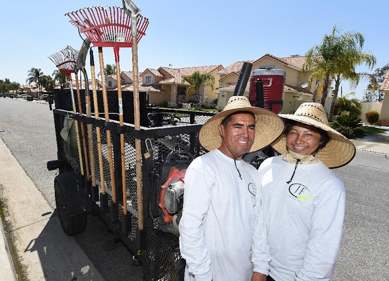 Jaime Flores (L) and his wife Ana Flores (R), migrants from Mexico who came to the United Sates 27 years ago, pose for a photo while doing landscape maintenance work, in Perris, California (AFP Photo/Robyn Beck)