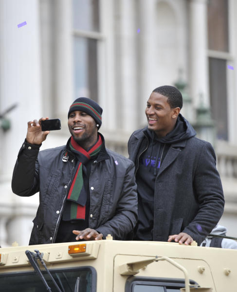 Baltimore Ravens wide receiver Anquan Boldin, left, takes photos as tight end Ed Dickson smiles during the Ravens victory parade Tuesday, Feb. 5, 2013, in Baltimore. The Ravens defeated the San Francisco 49ers in NFL football's Super Bowl XLVII 34-31 on Sunday. (AP Photo/Gail Burton)