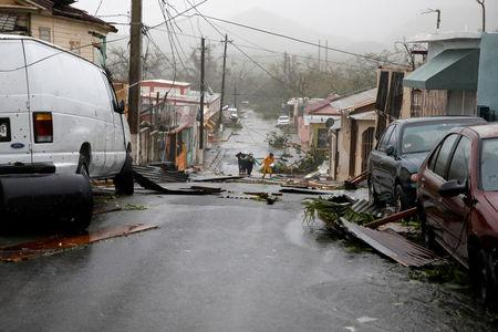 People walk on the street next to debris after the area was hit by Hurricane Maria in Guayama, Puerto Rico September 20, 2017. REUTERS/Carlos Garcia Rawlins