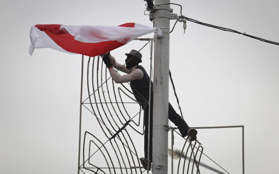 A man in a mask hangs an old Belarusian flag on a light pole during an opposition rally to protest the official presidential election results in Minsk, Belarus, Sunday, Sept. 27, 2020. Hundreds of thousands of Belarusians have been protesting daily since the Aug. 9 presidential election. (AP Photo/TUT.by)