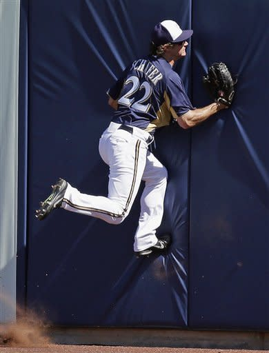 Milwaukee Brewers' Logan Schafer (22) goes up the wall to get a ball hit by Los Angeles Angels' Howard Kendrick during the first inning of an exhibition spring training baseball game on Saturday, March 2, 2013, in Phoenix. (AP Photo/Morry Gash)