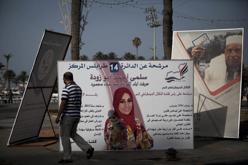 A Libyan man walks near National Assembly election campaign posters at Martyr's Square in Tripoli, Libya, Thursday, July 5, 2012. The Libyan National Assembly elections will take place on July 7, 2012, the first free elections since 1969. (AP Photo/Manu Brabo)