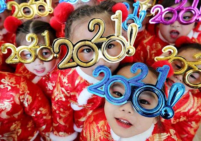 Children wearing glasses featuring number '2021' pose for a photo to welcome the New Year in Zaozhuang, Shandong Province of China (VCG via Getty Images)