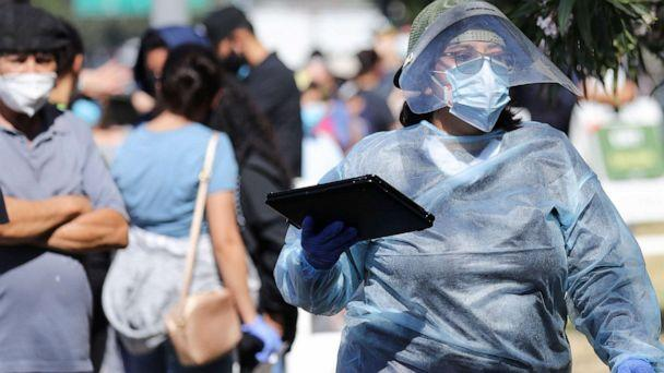 PHOTO: A worker in personal protective equipment (PPE) helps check in people at a COVID-19 testing center at Lincoln Park, July 7, 2020 in Los Angeles, during a spike in new coronavirus cases in California. (Mario Tama/Getty Images)