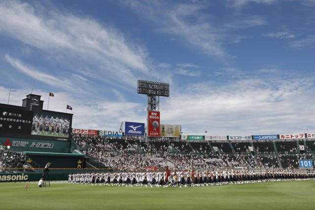 In this Aug. 2019, photo, baseball players parade during the opening ceremony of the summer high school baseball tournament at Koshien stadium in Nishinomiya, western Japan. Japan's beloved baseball tournament was canceled on Wednesday, May 20, 2020, because of the coronavirus pandemic. (Kyodo News via AP)