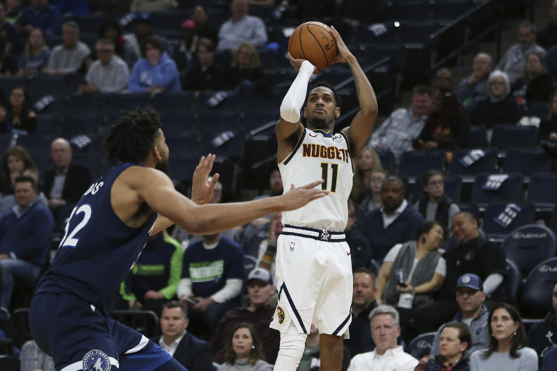 Denver Nuggets' Monte Morris lines up a shot against Minnesota Timberwolves' Karl-Anthony Towns in the second half of an NBA basketball game Monday, Jan. 20, 2020, in Minneapolis. Denver won 107-100. (AP Photo/Stacy Bengs)