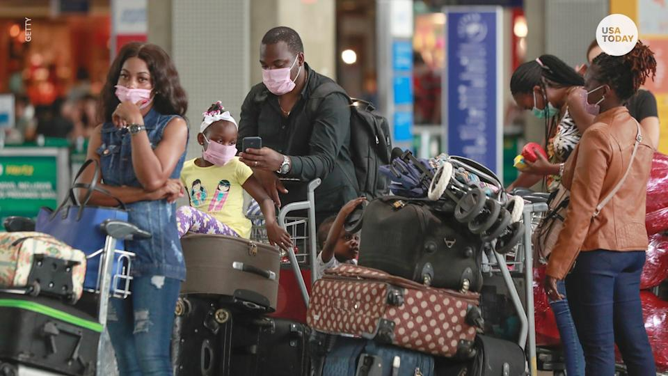 People wear masks at an airport.