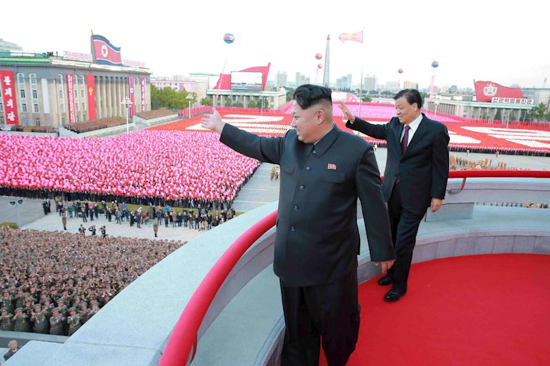 North Korean leader Kim Jong Un (L) and senior Chinese Communist Party official Liu Yunshan (R) wave during celebration of the 70th anniversary of the founding of the ruling Workers' Party of Korea