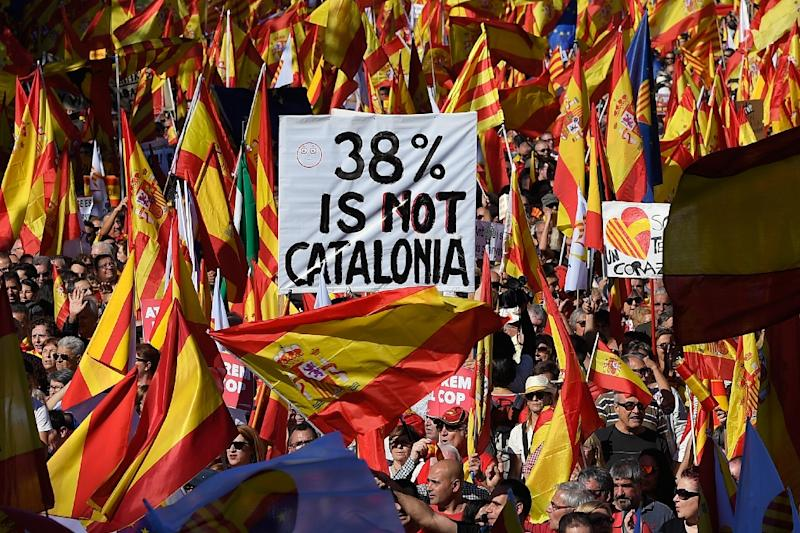 Protesters wave Spanish and Catalan Senyera flag while holding a sign reading