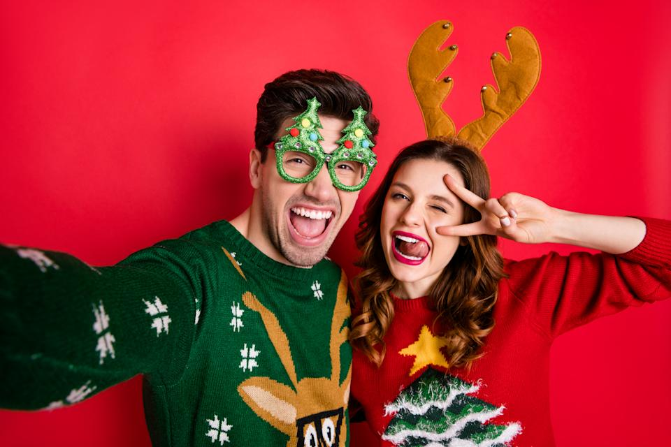 Photo of crazy couple making selfies sticking tongues winking eyes v-signing, wear funky ugly ornaments jumpers isolated red color background