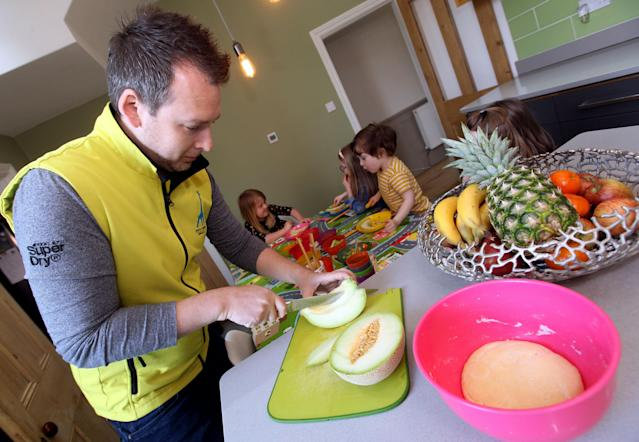 Sam Mills cutting up up fruit for the children he looks after. [Photo: Caters]