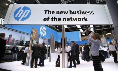 A visitor takes a photo with a tablet in front of a Hewlett-Packard (HP) stand at the Mobile World Congress in Barcelona, February 27, 2014. REUTERS/Albert Gea/Files