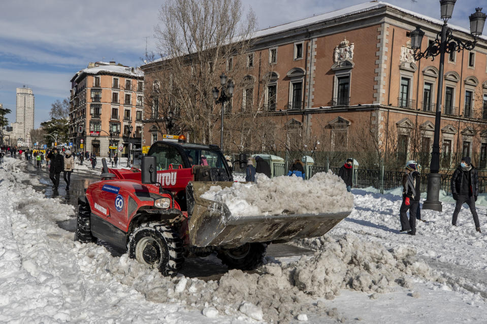 A plough clears snow in downtown Madrid, Spain, Sunday, Jan. 10, 2021. A large part of central Spain including the capital of Madrid are slowly clearing snow after the country's worst snowstorm in recent memory. (AP Photo/Manu Fernandez)