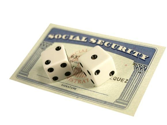 Social Security card with two dice on top of it.