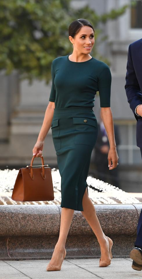 <p>Markle arrived in Dublin wearing her favourite go-to designer, Givenchy. Her forest green skirt ($2,140 CAD) and crew neck knit top (approximately $700) were paired with a tan leather purse by Strathberry (approximately $1,400 CAD) and nude heels by Paul Andrew (approximately $1,000 CAD). The Duchess also wore gold diamond clover earrings by Vanessa Tugendhaft (approximately $1,300 CAD).<br /><strong>Total cost of first look: $6,540 CAD</strong> </p>
