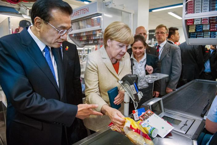Chinese Prime Minister Li Keqiang (L) and German Chancellor Angela Merkel (R) shop at a supermarket in Berlin on October 10, 2014 (AFP Photo/Lukas Schulze)