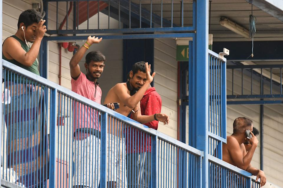 Foreign workers wave from the corridor of their rooms at the S11 Dormitory @ Punggol, where there are 62 cases of individuals with the COVID-19 novel coronavirus, in Singapore on April 6, 2020. (Photo by Roslan RAHMAN / AFP) (Photo by ROSLAN RAHMAN/AFP via Getty Images)