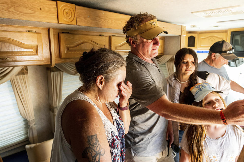 Kimberly Price wipes tears from her eyes while receiving a donated motorhome from EmergencyRV.org founder Woody Faircloth, center, on Sunday, Sept. 5, 2021, in Quincy, Calif. (AP Photo/Noah Berger)