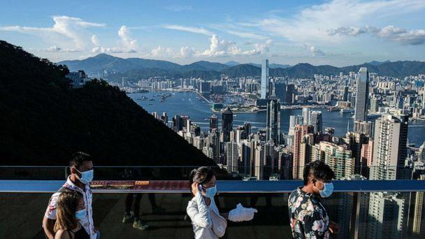 PHOTO: (FILES) In this file photo taken on July 28, 2020, visitors walk along a viewing platform on Victoria Peak in Hong Kong. - Hong Kong and Singapore announced on April 26, 2021 plans to resurrect their scrapped coronavirus travel bubble.  (Anthony Wallace/Afp/AFP via Getty Images)
