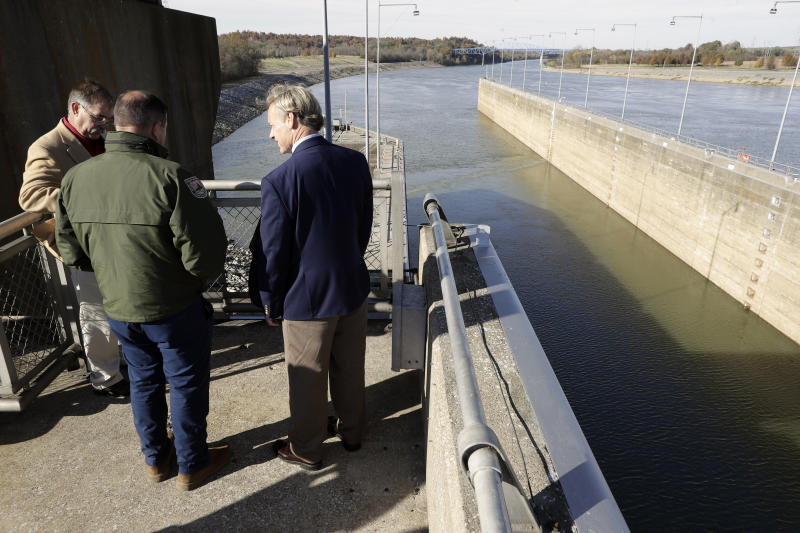People look over the Barkley Lock and Dam where the Cumberland River meets Lake Barkley, Friday, Nov. 8, 2019, in Grand Rivers, Ky. A noise-making, bubbling, bio-acoustic fish fence has been installed in the lock to deter the spread of destructive Asian carp . (AP Photo/Mark Humphrey)