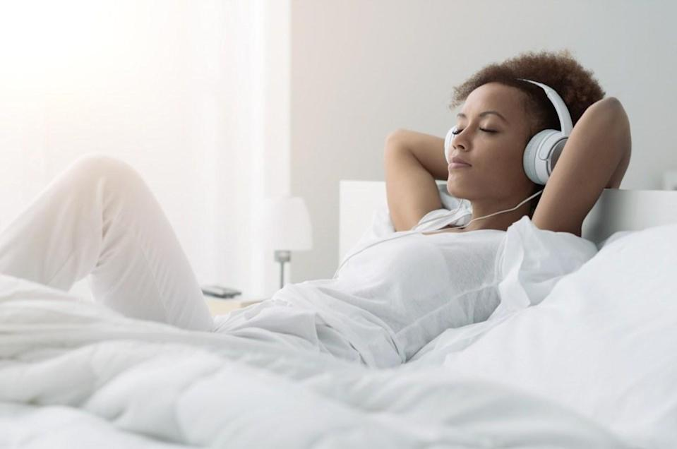 woman relaxing and listening to music using headphones, she is lying in bed