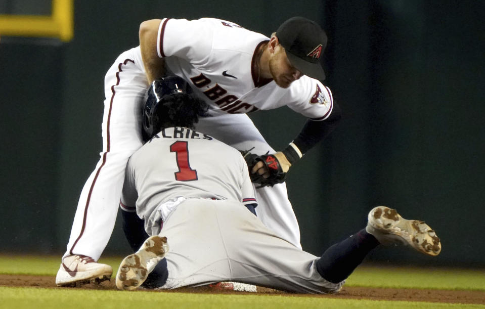 Atlanta Braves' Ozzie Albies (1) collides with Arizona Diamondbacks second baseman Josh VanMeter, top, during a steal-attempt in which he was out during the fifth inning of a baseball game Thursday, Sept 23, 2021, in Phoenix. (AP Photo/Darryl Webb)