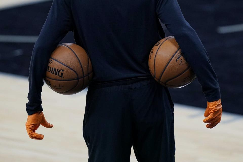 A man wears gloves and has a basketball tucked under each arm.