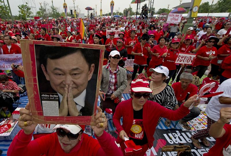 "A Thai pro-government ""Red Shirts"" protester holds a portrait of fugitive former premier Thaksin Shinawatra during a rally at Phutthamonthon suburb of Bangkok on April 5, 2014"